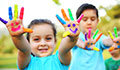 Two children holding up hands covered in finger paint