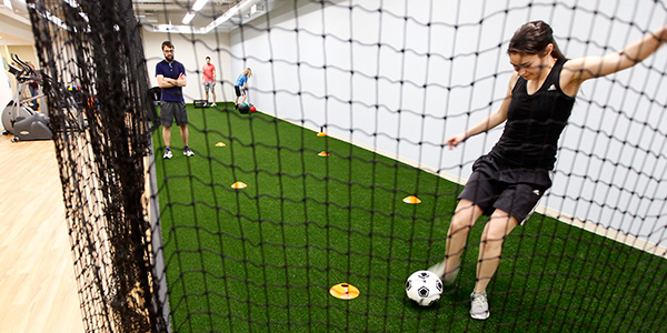 Patient kicking soccer ball into net during rehab