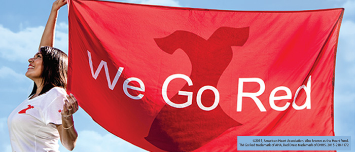 Woman holding a red We Go Red banner