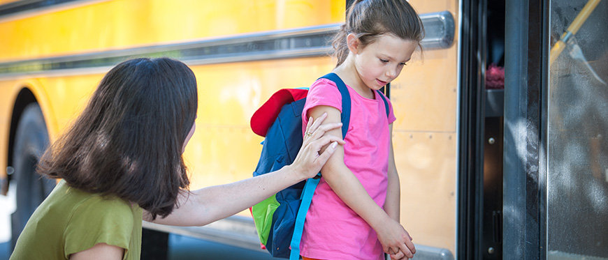 Anxious girl saying goodbye to mother before getting on school bus