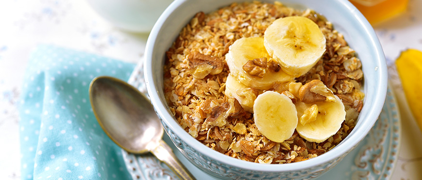 A bowl of oatmeal topped by slices of banana