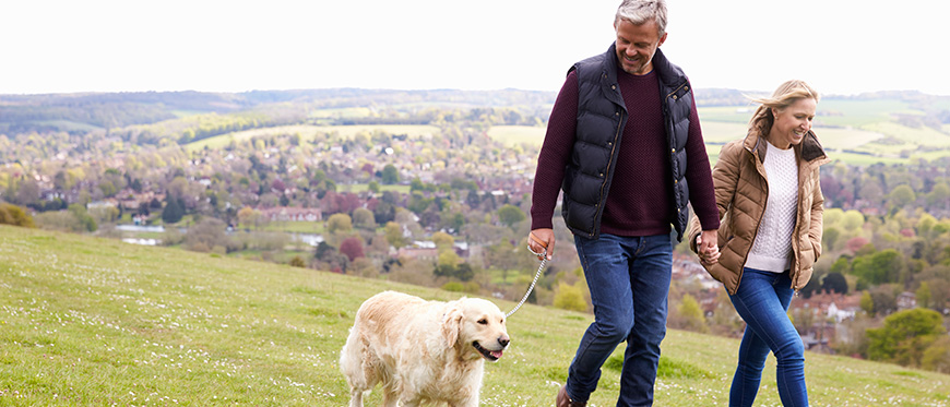 Older couple walking dog in field with hills in background