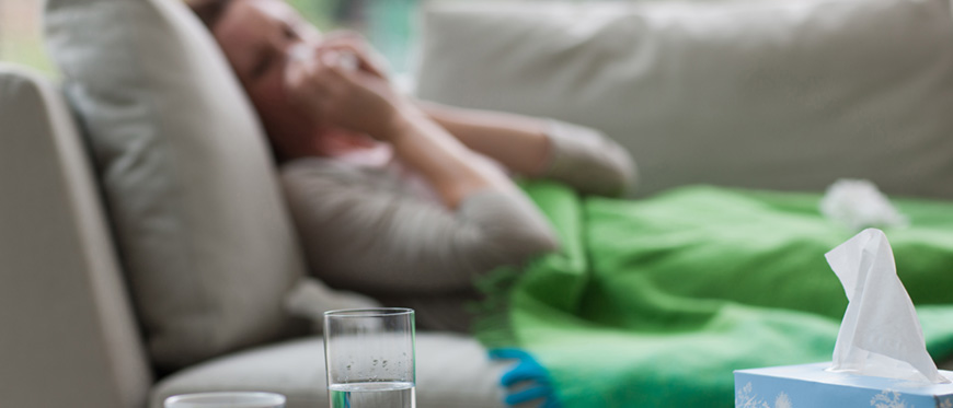 Woman blowing nose, lying sick on sofa