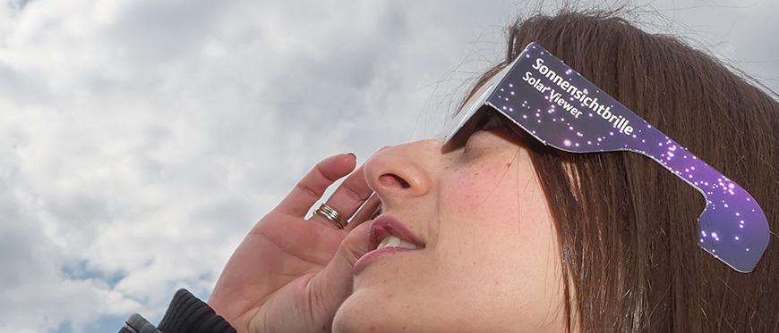 Women wearing solar eclipse glasses