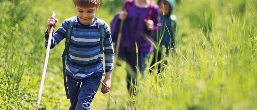 Kids walking through a grass field