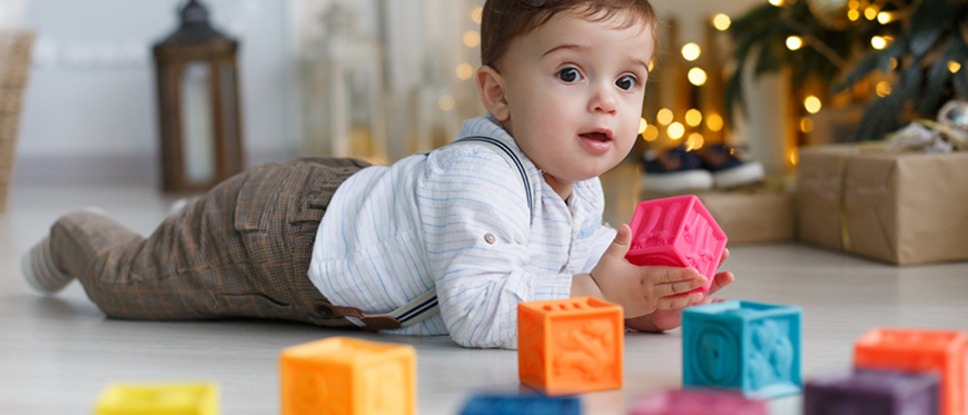 Toddler boy playing with plastic blocks in front of Christmas Tree
