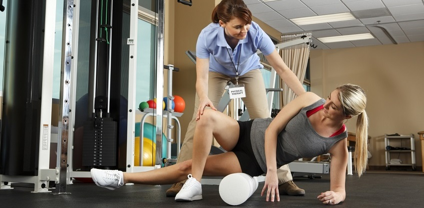 Physical therapist helping patient use foam roller in gym