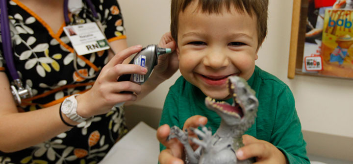 Smiling boy holding dinosaur while nurse checks his ears