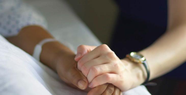 Nursing holding patient's hand.