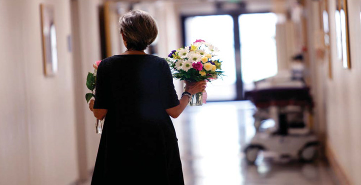 Women walking with flowers down a hospital corridor.