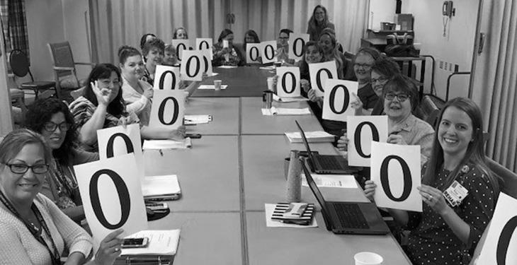 Woodridge employees hold up zeros to celebrate deficiency free rating