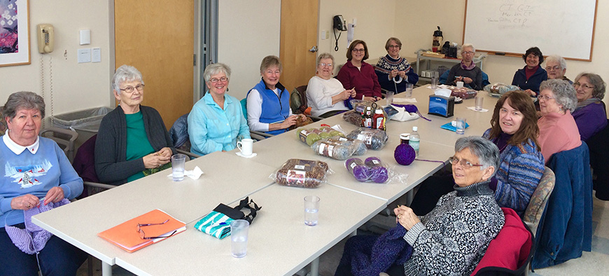 CVMC Volunteers Knitters gathered around table knitting