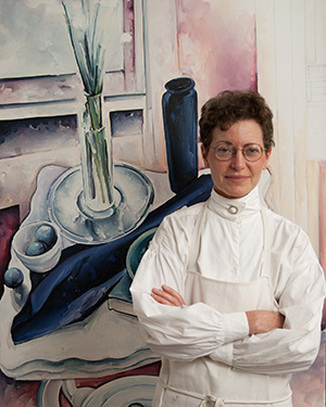 Margaret Sparrow standing in front of one of her paintings