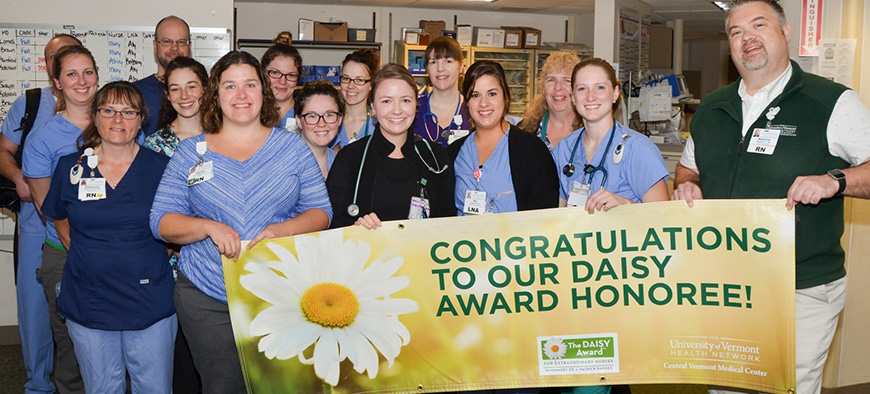 Group of CVMC nurses hold up Daisy Award banner