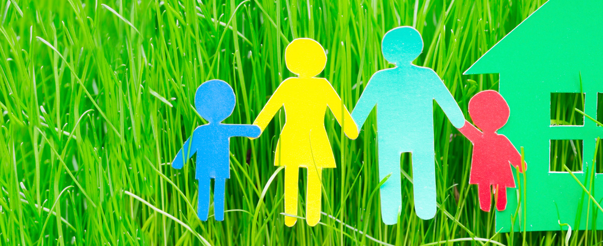 Colorful paper cutout family next to cutout house on green grass