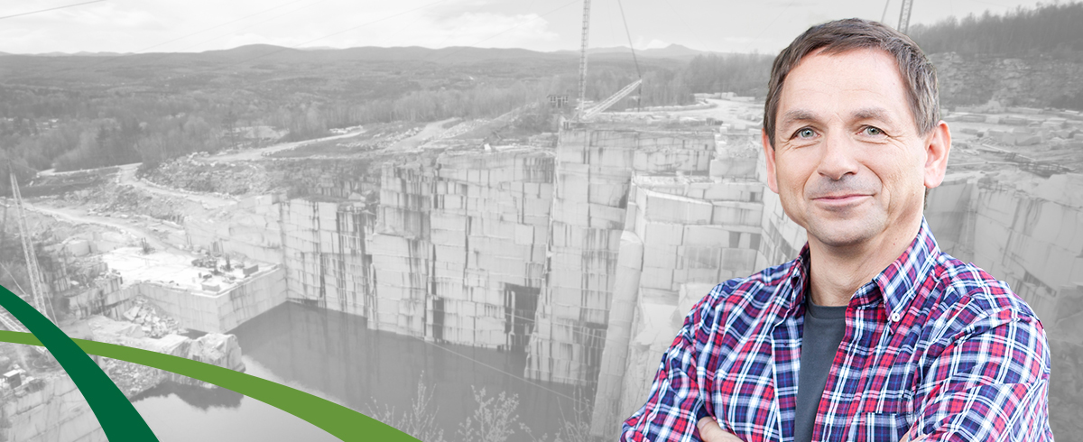 Man set in front of black and white photo of Rock of Ages granite quarry