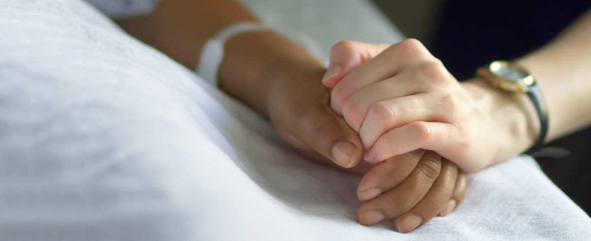 Close up of nursing holding patient's hand