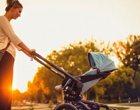 Woman pushing a stroller with sun setting