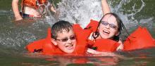 Kids swimming in lake with orange life jackets