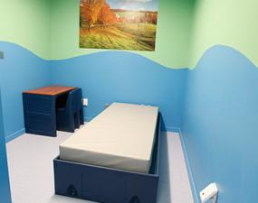 A bed in ED room with blue and green painted walls
