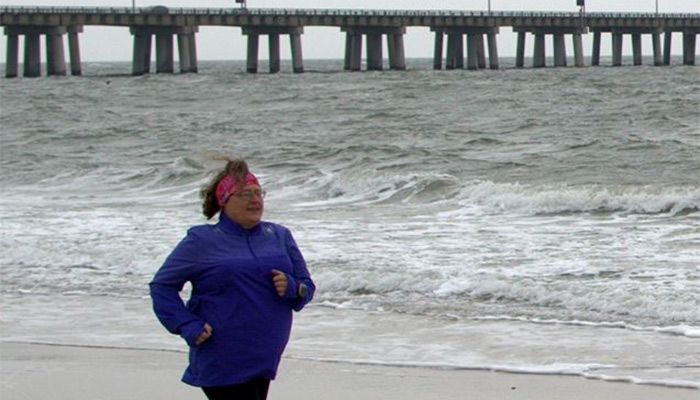 Candace Brown running on beach in Virginia at the end of February